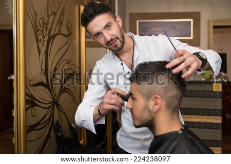Hairdresser Cleaning Young Man After Haircut - Handsome Young Hairdresser Giving A New Haircut To Male Customer At Parlor - stock photo
