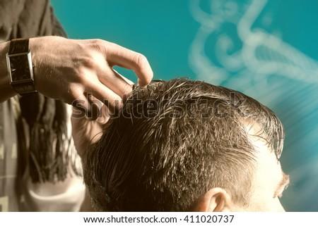Hairdresser combing hair brunet man - stock photo