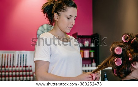 Hairdresser curling woman hair in a beauty salon - stock photo