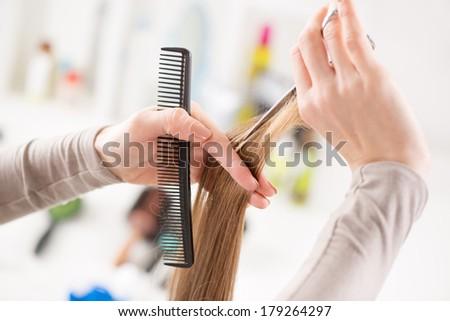 Hairdresser cut hair of a woman. - stock photo