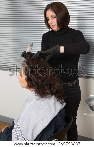 Hairdresser cutting client's hair in beauty salon. - stock photo