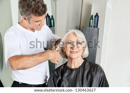 Hairdresser cutting senior client's hair at beauty salon - stock photo