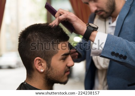 Hairdresser Do Haircut Close Up Indoor Shot - Handsome Young Hairdresser Giving A New Haircut To Male Customer At Parlor - stock photo