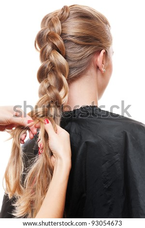 hairdresser doing up one's hair in a plait. isolated on white background - stock photo