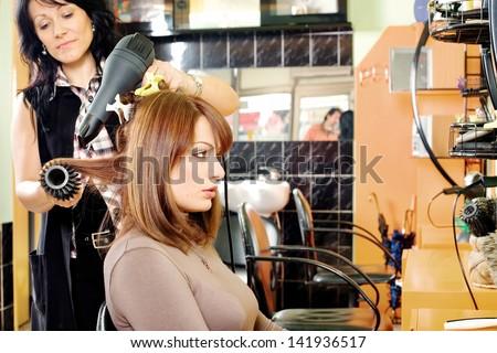 hairdresser dries hair in a hair salon - stock photo