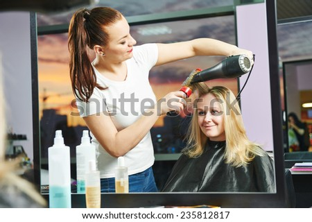hairdresser drying hair with blow dryer of woman client at beauty parlour after highlighting - stock photo