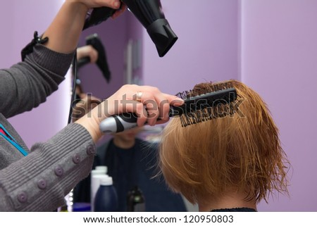 Hairdresser drying woman's hair in beauty salon - stock photo