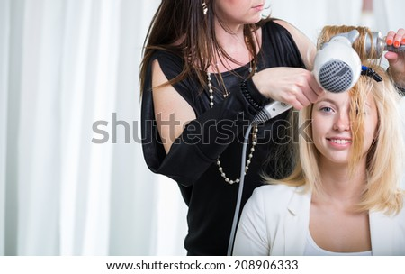 Hairdresser/Hairstyle artist working on a young woman's hair, giving it shape and volume - stock photo