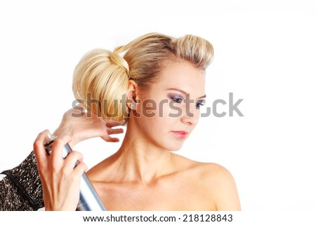 Hairdresser  hand using hairspray on model adjusting hair dress - stock photo