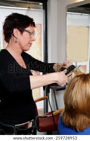 hairdresser is brushing hair of a blond woman