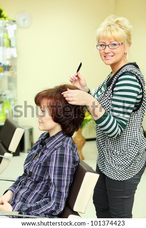 Hairdresser makes hair styling for woman by rake-comb and looks at camera in beauty salon - stock photo