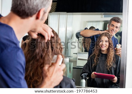 Hairdresser setting up client's hair while looking at mirror in salon - stock photo