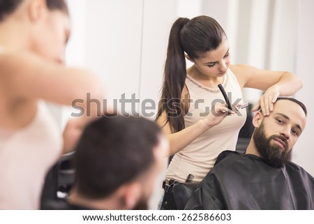 Hairdresser shaving  an old-fashioned razor and combs of satisfied client in professional hairdressing salon. - stock photo