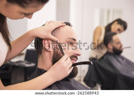 Hairdresser shaving an old-fashioned razor of satisfied client in professional hairdressing salon. - stock photo