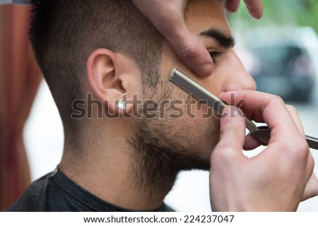 Hairdresser Shaving Man's Chin With A Straight Razor - Handsome Young Hairdresser Giving A New Haircut To Male Customer At Parlor - stock photo