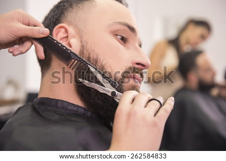 Hairdresser shaving  with scissors and combs ofclient in professional hairdressing salon. - stock photo