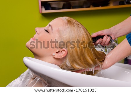 Hairdresser washing blond haired woman in the barber  - stock photo