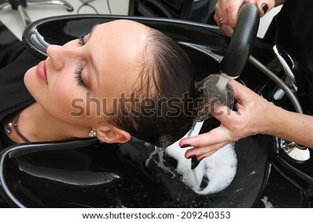 Hairdresser washing woman's hair under the tap - stock photo