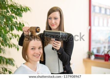 Hairdresser with a barrel brush and a blow-dryer styling a customers hair - stock photo