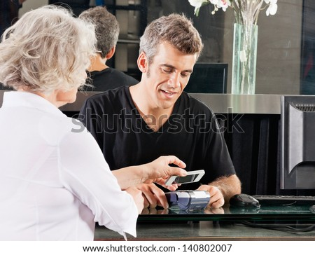 Hairdresser with female client paying with mobilephone over electronic reader at counter - stock photo