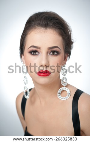 Hairstyle and make up - beautiful female art portrait with earrings. Elegance. Genuine natural brunette with jewelries in studio. Portrait of a attractive woman with red lips and creative makeup - stock photo