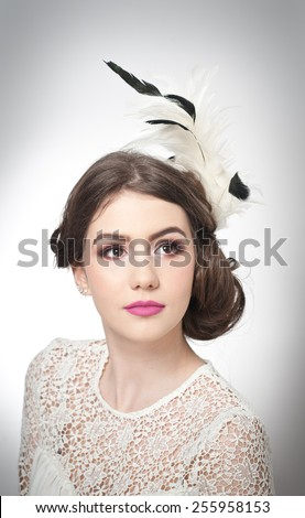 Hairstyle and make up - beautiful young girl art portrait. Genuine natural brunette with creative haircut, studio shot. Attractive female with beautiful lips and eyes in white lace blouse, over white - stock photo
