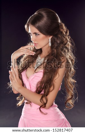 Hairstyle. Long wavy hair. Fashion photo of young woman. Sexy Girl posing in pink dress isolated on dark background. Studio - stock photo