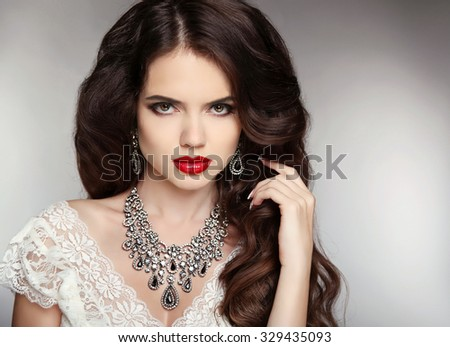 Hairstyle. Makeup. Jewelry. Beautiful woman with curly hair and evening make-up. Beauty fashion girl portrait. Elegant lady with diamond pendant. - stock photo