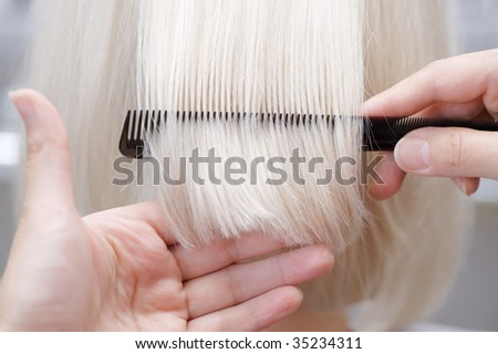 Hairstylist combing hair - stock photo