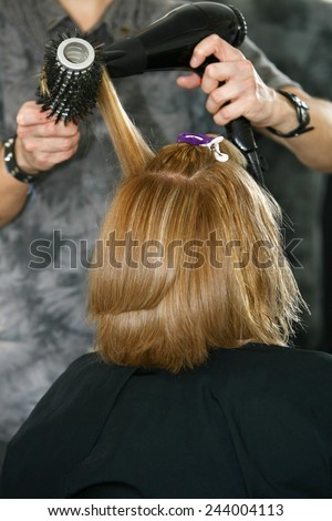 Hairstylist Drying woman Hair in Salon for short hair - stock photo