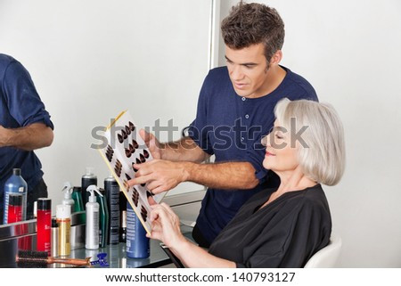 Hairstylist with catalog choosing hair color for female customer at parlor - stock photo