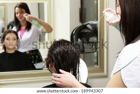 Hairstylist with hairspray spraying hair of female client. Woman in hairdressing beauty salon. - stock photo