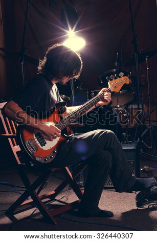 hairy guy playing bass guitar - stock photo