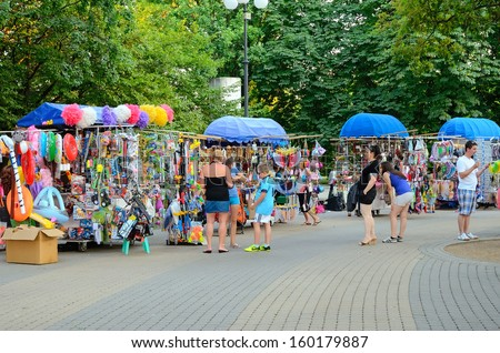HAJDUSZOBOSZLO, HUNGARY - JULY 23: Tourists are shopping on street of Hajduszoboszlo, Hungary on July 23, 2013.Hajduszoboszlo is a popular spa resort in Hungary. It is located 202 km east of Budapest. - stock photo