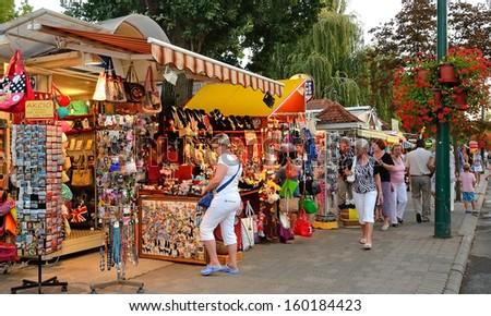 HAJDUSZOBOSZLO, HUNGARY - JULY 26: Tourists are shopping on street of Hajduszoboszlo, Hungary on July 26, 2013. Hajduszoboszlo is popular spa resort in Hungary. It is located 202 km east of Budapest. - stock photo