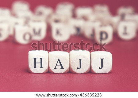 Hajj word written on wood cube with red background - stock photo