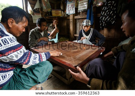 HAKHA, MYANMAR - JUNE 19 2015: Local men play Carrom's in the Hakha region in Chin State, Myanmar. - stock photo