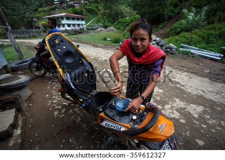 HAKHA, MYANMAR - JUNE 19 2015: Local woman filling petrol in the Hakha region in Chin State, Myanmar. - stock photo