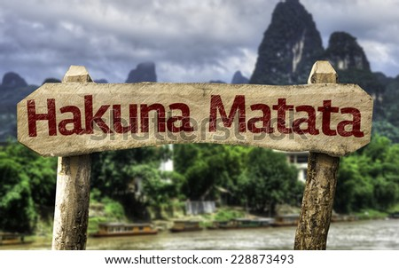 "Hakuna Matata (Swahili phrase; it means ""no worries"") sign with a forest background - stock photo"