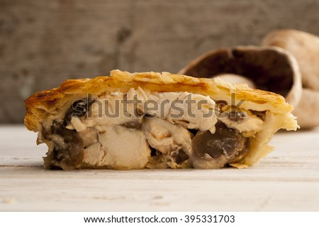 Half a chicken and mushroom pie with fresh mushrooms in the background. - stock photo