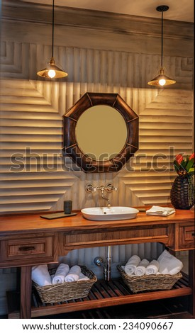 Half-bathroom with vanity and mirror in luxury home - stock photo