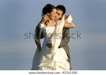 Half body portrait of newlywed young couple embracing with ,gray background. - stock photo