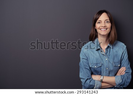 Half Body Shot of a Cheerful Woman in Denim Shirt, Smiling at the Camera with Arms Crossed Against Gray Wall Background with Copy Space. - stock photo