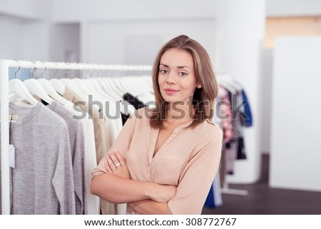 Half Body Shot of a Confident Pretty Young Woman inside a Clothing Store, Smiling at the Camera with Arms Crossing Over her Stomach. - stock photo