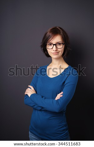 Half Body Shot of a Confident Young Woman with Eyeglasses Smiling at the Camera with Arms Crossing Over her Chest Against Gray Wall Background - stock photo