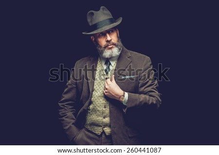 Half Body Shot of a Goatee Adult Man Wearing Formal Wear with Hat Looking to the Right of the Frame on a Black Background. - stock photo