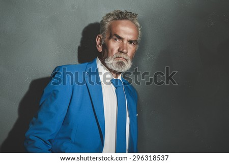 Half Body Shot of a Pensive Matured Businessman in Blue Coat, Leaning Against the Gray Wall and Looking Into the Distance. - stock photo