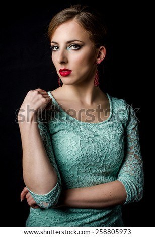 Half Body Shot of a Pretty Young Woman Posing in Mint Green Dress with One Hand on the Shoulder and Staring at the Camera on a Black Background. - stock photo