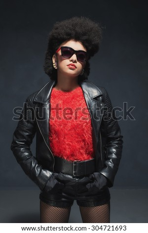 Half Body Shot of a Stylish Young Woman Wearing Black Leather Jacket with Sunglasses Against Black Background. - stock photo