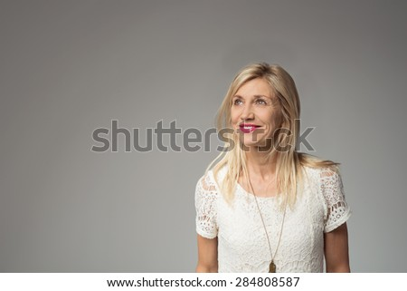 Half Body Shot of a Thoughtful Pretty Adult Woman with Blond Hair, Looking Up with a Smile Against Gray Background with Copy Space. - stock photo